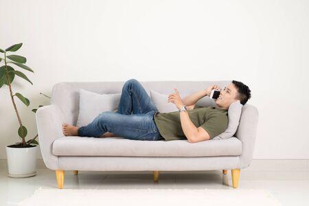 Ontspannen man met behulp van een slimme telefoon liggend op een bank/bank in de woonkamer thuis
