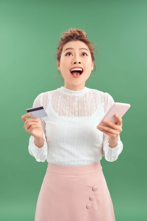 Excited young Asian lady isolated over green background using mobile phone holding credit card.