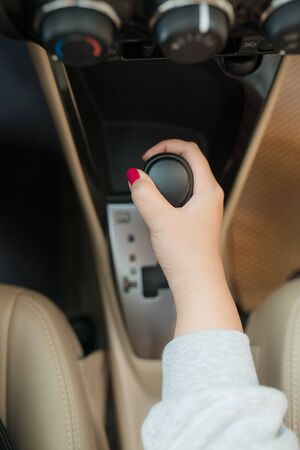 woman switches the automatic transmissions close-up. Close-up of the drivers adm includes mode Drive on the gear lever automatic transmission of the car interior parts