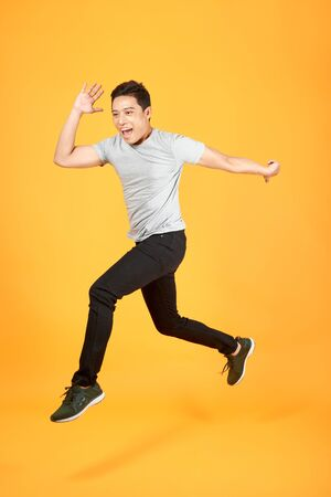 Handsome jumping Asian man on color background