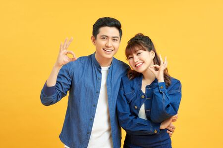 Beautiful young couple together standing over isolated yellow background looking surprised and shocked doing ok approval symbol with fingers. Crazy expression