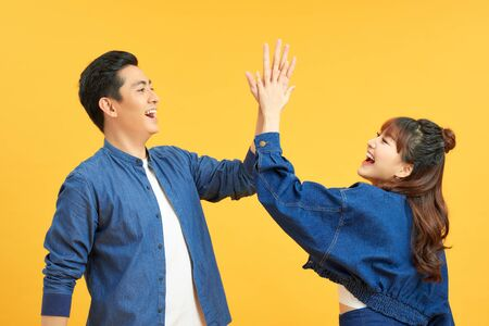 Positive junge Paare geben High Five, stimmen zu, als Team zu arbeiten, seitlich zu stehen, isoliert auf gelber Wand.