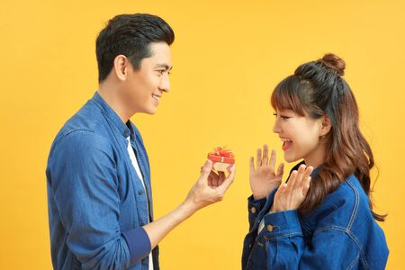 Young handsome asian man surprisingly ask her girlfriend for proposal. Фото со стока