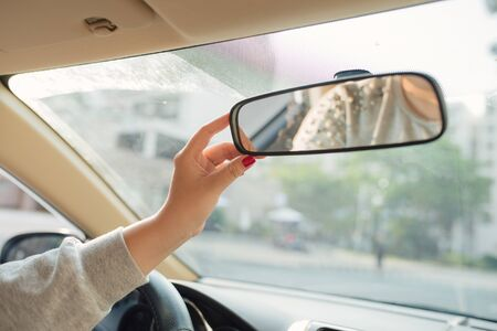 Woman hands adjusting rear view mirror in the car
