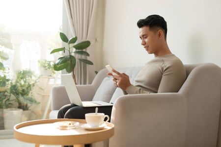 Young Asian man relaxing at home on a sofa with his laptop computer chatting on his mobile while reading the screen of the laptop with a smile