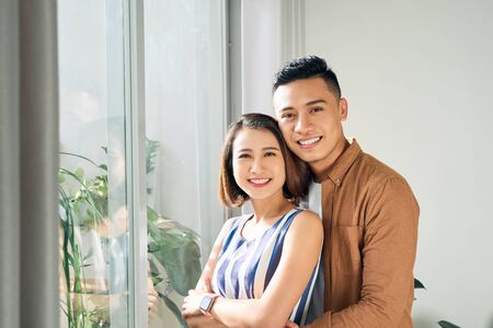 Happy young Asian couple embracing near the window Imagens