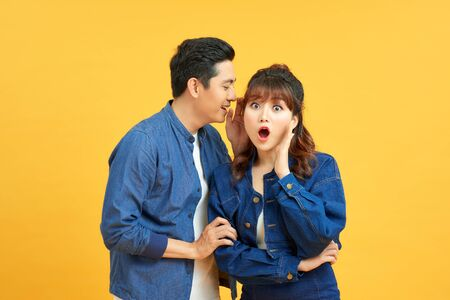 Portrait of asian man whispering secret or interesting gossip to excited woman in her ear isolated over yellow background