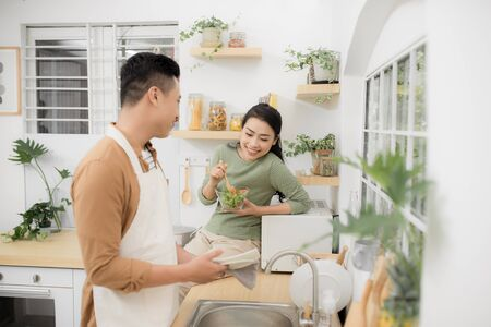 Asian couple eating breakfast early in the morning in the kitchen and having a good time.