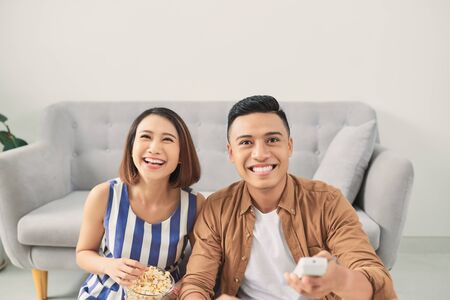 Happy young Asian couple watching tv at home