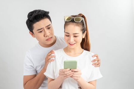 Asian young boy spying on his partner's mobile phone in white background isolated