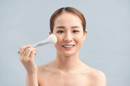 Closeup Of Beautiful Young Female Model Putting Blush With Cosmetic Brush. Foto de archivo
