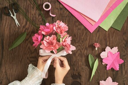 Woman making paper bouquet at wood table with color papers, scissors for valentines, holidays. Flatlay, top view. Banco de Imagens