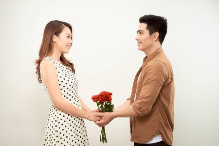 Elegant couple of young lovers holding hands, a girl holding a large bouquet of red roses. Valentine's Day.