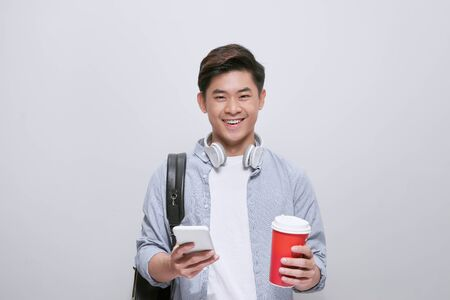 handsome young man write sms and drink coffee