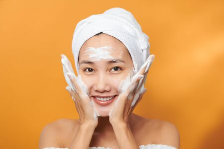 Happy young Asian woman applying face cream while wearing a towel and touching her face. Isolated on orange background