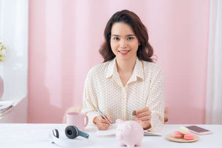 Portrait of young Asian woman putting coin in piggy bank and writing report.