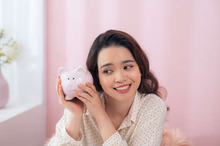 Beautiful young Asian woman holding piggy bank over pink background.
