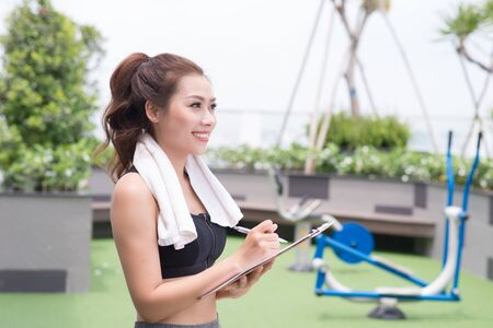 A pretty young asian female fitness trainer taking some notes while at the park