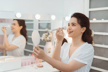 Happy Girl gets blush on the cheekbones. Powder, rouge make-up