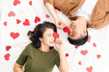 Smiling young couple lying on bed with many heart shapes.