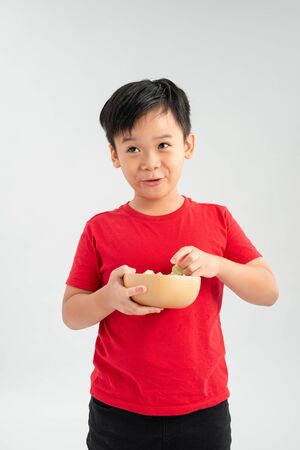 Schoolboy holds a yellow bowl full of candy. Portrait of a child of asian appearance and delicious food