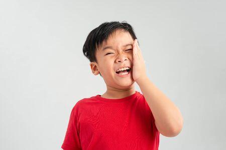 Little boy having toothache. Emotional portrait of asian boy suffering. Sad child with tooth pain. Dental problem Standard-Bild