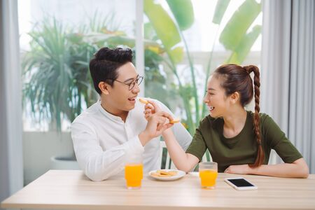 Young couple having fun while having breakfast feeding each other