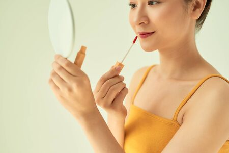Closeup of Asian young female applying lipstick with mirror against light background. Stock Photo