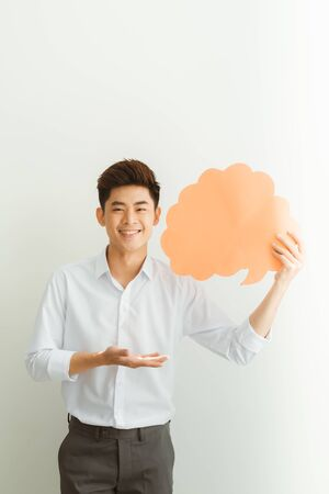 Portrait of an excited young  man holding empty speech bubble isolated over white background