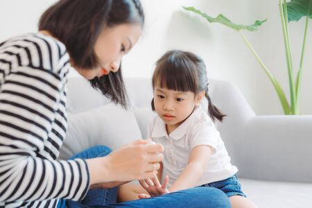 Cute daughter with mother making manicure at home