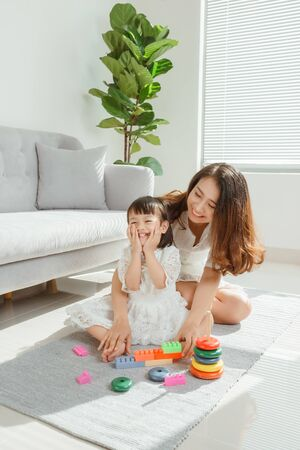 Madre e hija juegan un juguete y se divierten en la sala de estar