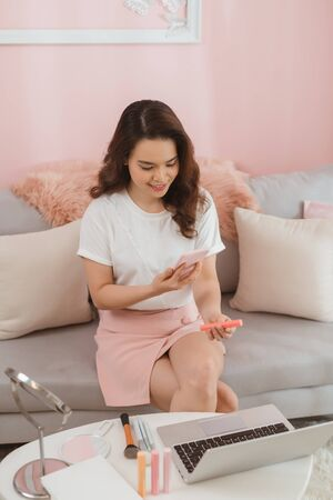 asian smiling girl using smartphone to shoot lipstick posted for sale on the internet. Startup small business owner working with tablet at workplace