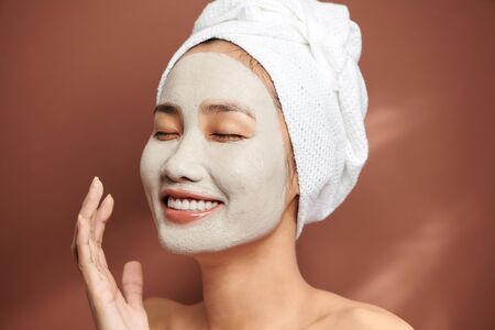 Happy young woman smiling and wearing white towel and has a facial mask.