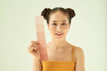 Portrait of young beautiful Asian woman showing skin color palette over light background.