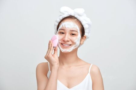 Happy young Asian woman applying foaming cleanser on her face and wearing towel on her head. Banque d'images