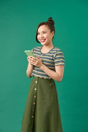 Portrait of a smiling casual woman holding smartphone over green background Foto de archivo