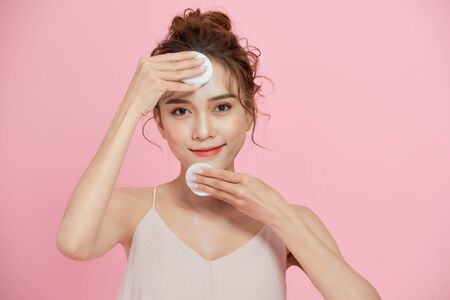 Close up beauty portrait of a smiling attractive woman cleaning her face with a cotton pad isolated over pink background