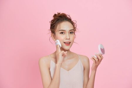 Portrait of beautiful asian woman applying powder puff at cheek makeup of cosmetic isolated over pink background.