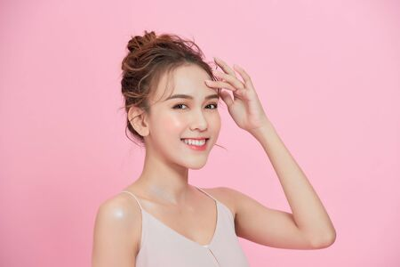 Beautiful happy woman face cosmetic concept healthy clean skin natural isolated over pink background.