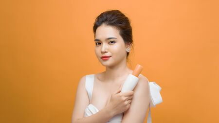 Portrait of Asian woman holding beauty product over yellow background