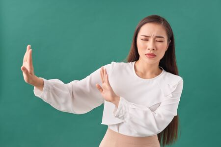 Young woman isolated on turquoise background being shocked due to an imminent danger 免版税图像
