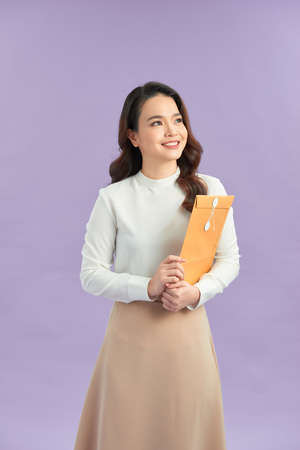 Woman hand holding brown envelope on purple background
