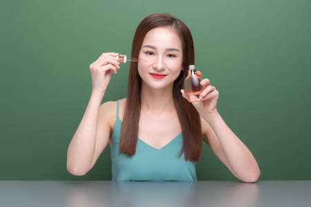 Beautiful Asian woman applying cosmetic skin serum treatment isolated on green background.