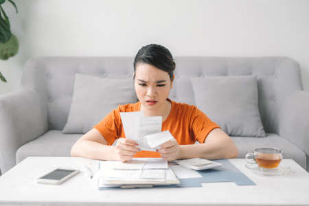 Sad woman looking at monthly bills Banque d'images - 151496806