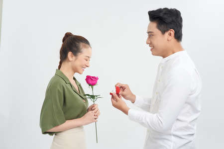 Attractive young woman is standing with roses in hands while handsome man is making proposal with ring in hands.