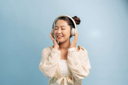 Peaceful good looking magnetic lady standing isolated over blue background, closing eyes, holding headphones, listening to music