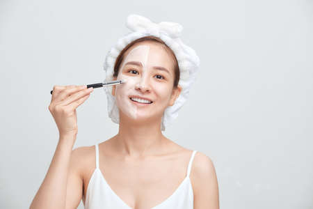 Young Asian woman applying facial clay mask against white background.