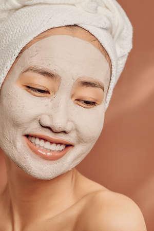 Young Asian woman enjoying of a facial mask treatment.