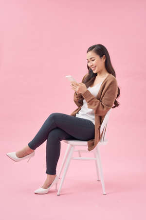 Portrait of a satisfied casual asian woman using mobile phone while sitting on a chair over pink background Foto de archivo