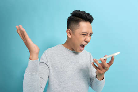 You will have problems man! Angry confused aggressive in bad mood guy shouting threatening in the loudspeaker of his smartphone Archivio Fotografico